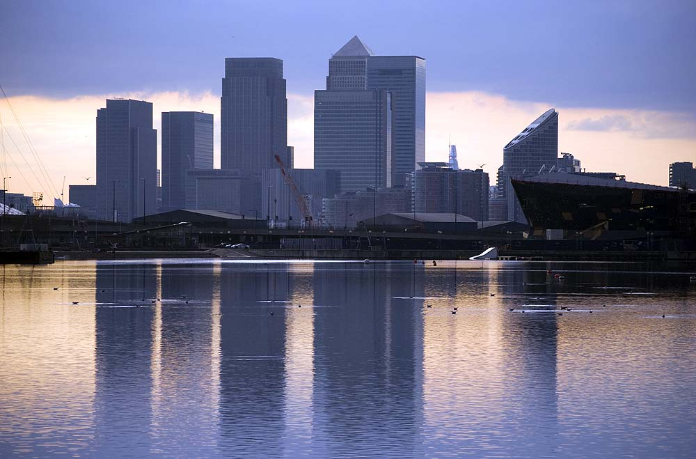 blue tone of canary wharf silhouette over canal at sunset